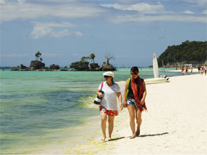 Two tourists walking along White Beach, Boracay Island, Philippines